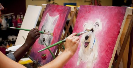 woman painting dog portrait in paint and sip class